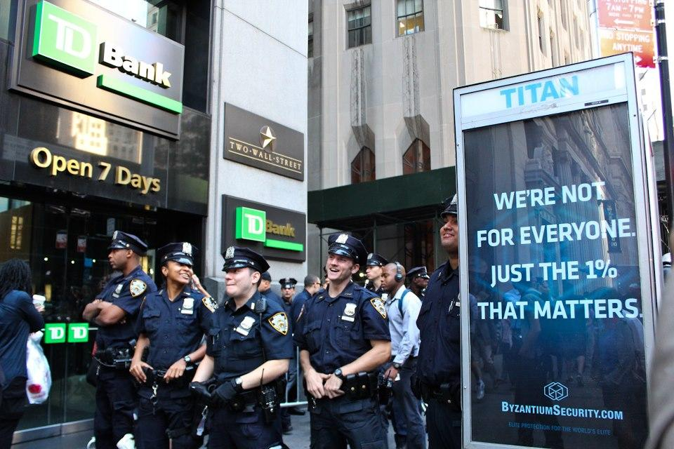New York City cops snicker around a financial services company banner reading 'we're for the 1 percent'