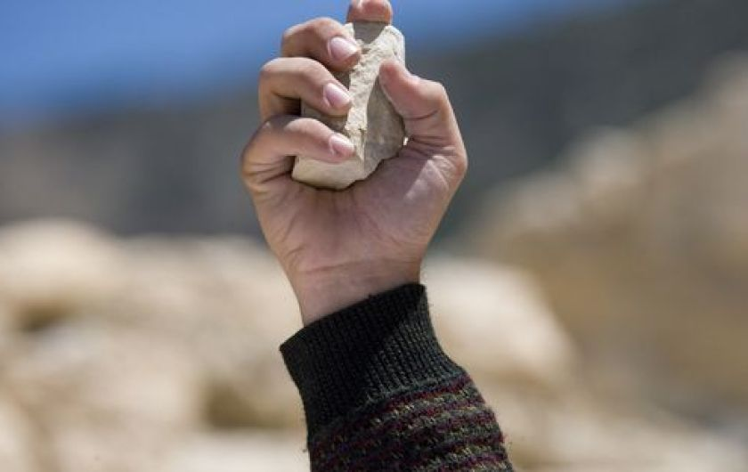 photo of hand holding rock